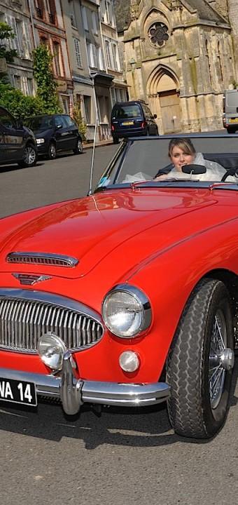 La mariée et le marié partent pour une séance de photo avec leur voiture