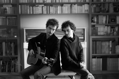 photo d'un homme jouant de la guitare et un autre assis, Damien et Renan Luce