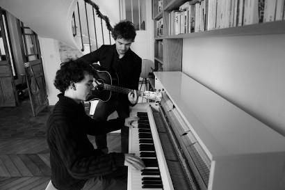 photo en noir et blanc de deux hommes en train de jouer du piano et de la guitare, Damien et Renan Luce
